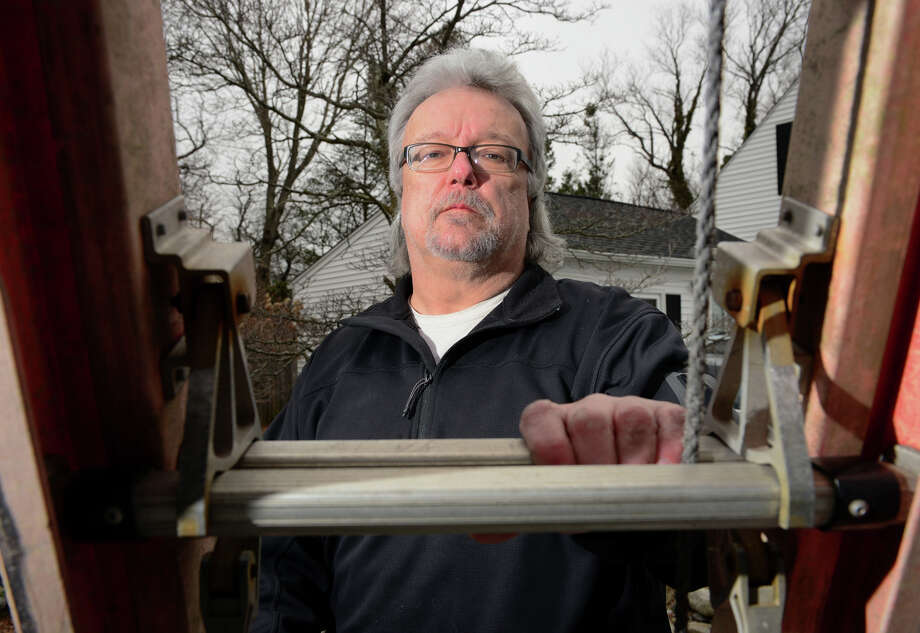 Stan Bajerski, of Houseworks Home Inspections, poses with one of his ladders that he uses on the job in Milford, Conn., on Tuesday Mar. 31, 2015. Bajerski is also president of the Connecticut Association of Home Inspectors. Photo: Christian Abraham / Connecticut Post