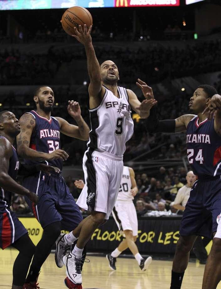 Spurs' Tony Parker (09) splits the defense of Atlanta Hawks' Mike Scott (32) and Kent Bazemore (24) at the AT&T Center on Wednesday, Nov. 5, 2014. (Kin Man Hui/San Antonio Express-News) Photo: San Antonio Express-News
