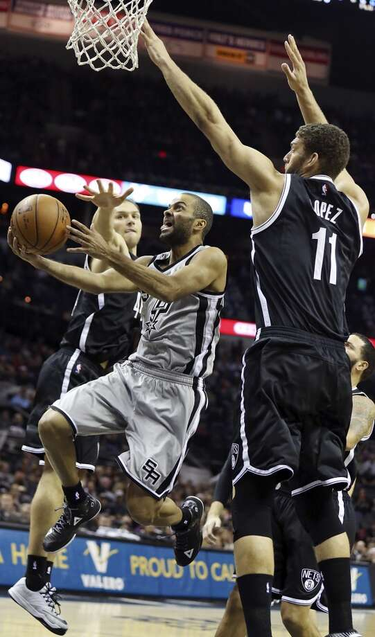 San Antonio Spurs' Tony Parker drives to the basket between Brooklyn Nets' Bojan Bogdanovic (left) and Brook Lopez during first half action Saturday Nov. 22, 2014 at the AT&T Center. Photo: San Antonio Express-News