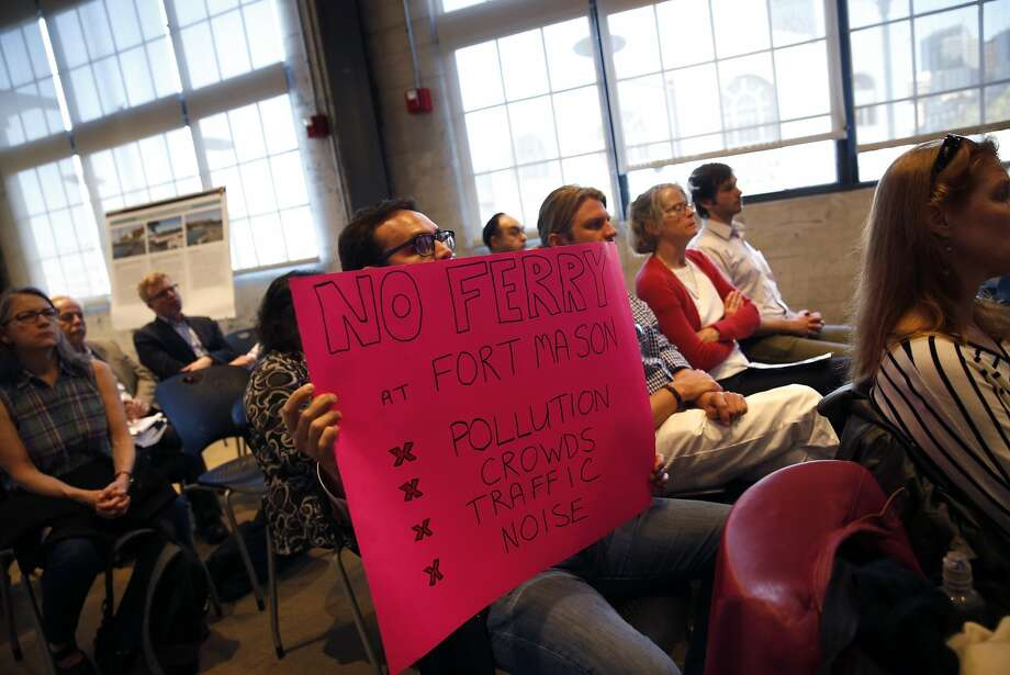 """San Francisco resident Tony Gilbert holds a """"No Ferry"""" sign as National Park Service Acting Superintendent Aaron Roth discusses proposals to relocate Alcatraz ferry during public meeting at Pier 1 in San Francisco, Calif., on Tuesday, March 31, 2015. Photo: Scott Strazzante, The Chronicle"""