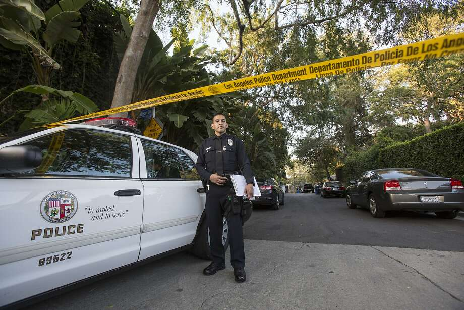 An officer stands outside a home in the Hollywood Hills area of Los Angeles, Tuesday, March 31, 2015. Police say a man was found dead at the home of Andrew Getty, heir to Getty oil fortune. (AP Photo/Ringo H.W. Chiu) Photo: Ringo H.W. Chiu, Associated Press