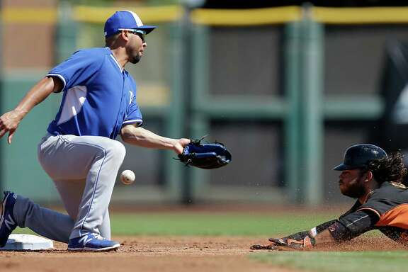 Giants shortstop Brandon Crawford steals second base in a Cactus League game last month as the Royals' Omar Infante misses the ball.