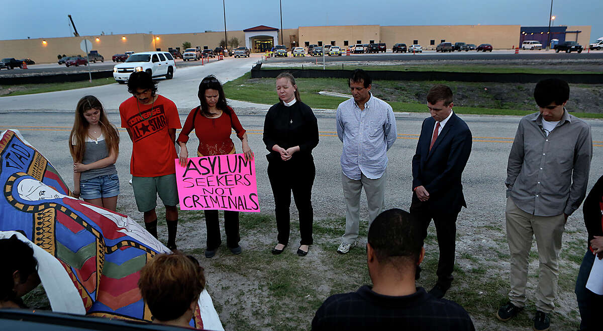 Rev. Traci Smith, center, of Northwood Presbyterian Church, leads a group of 30 in prayer as they hold a vigil in support of mothers in the Karnes County Residential Center that are on a hunger strike opposing their continued detention. Tuesday, March 31, 2015.