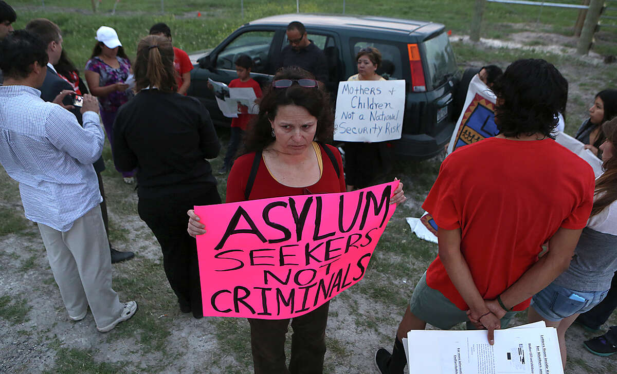 Marisa Laufer holds a sign as a group of 30 hold a vigil in support of mothers in the Karnes County Residential Center that are on a hunger strike opposing their continued detention. Tuesday, March 31, 2015.
