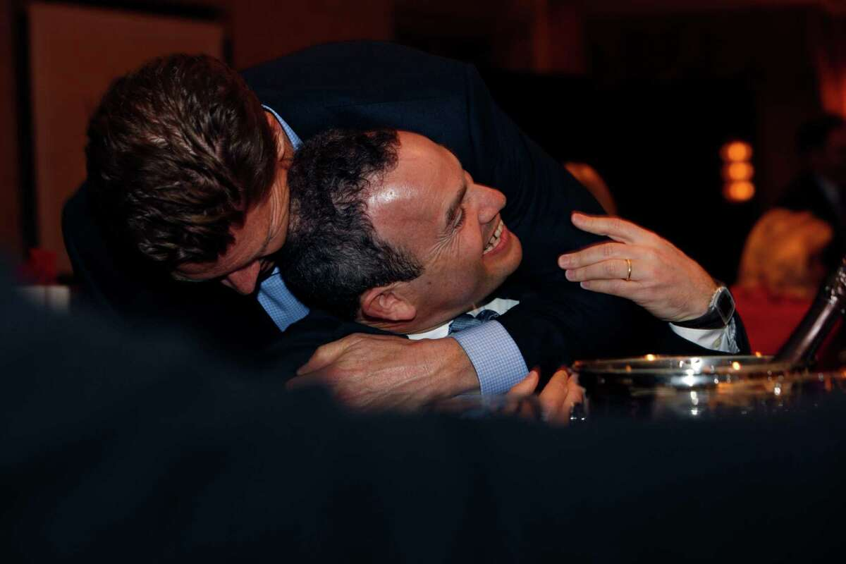After being named the San Francisco Chronicle's Visionary of the Year recipient at the Fairmont Hotel, Evan Marwell (center), CEO and founder of EducationSuperHighway is hugged by Matt Roberts, CEO of OpenTable, Tuesday, March 31, 2015, in San Francisco, Calif.