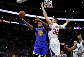 Golden State Warriors' Marreese Speights, left, goes to the hoop while Los Angeles Clippers' Blake Griffin, right, defends during the second half of an NBA basketball game, Tuesday, March 31, 2015, in Los Angeles. (AP Photo/Danny Moloshok)