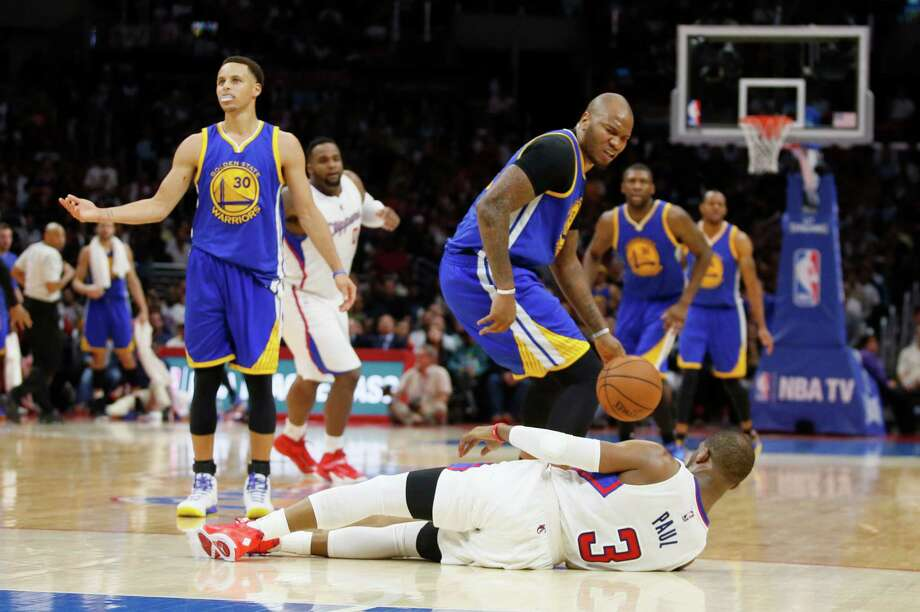 Golden State Warriors' Marreese Speights, center, is called for a personal foul and technical foul while looking down at Los Angeles Clippers' Chris Paul, bottom, after colliding with him as Paul dribbled the ball down the court during the second half of an NBA basketball game, Tuesday, March 31, 2015, in Los Angeles. Also looking on are Golden State Warriors' Stephen Curry, left, Los Angeles Clippers' Glen Davis, second left, and Warriors' Festus Ezeli, right. (AP Photo/Danny Moloshok) Photo: Danny Moloshok / Associated Press / FR161655 AP