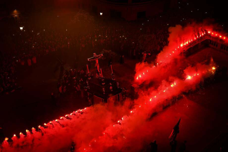 Red flares burn while penitents of the Cristo de Viga brotherhood carrying a float with a cross take part in a Holy Week procession in Jerez de la Frontera, Spain, Monday, March 30, 2015. Hundreds of processions take place throughout Spain during the Easter Holy Week. (AP Photo/Daniel Ochoa de Olza) Photo: Daniel Ochoa De Olza, Associated Press