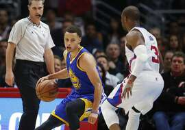 Golden State Warriors' Stephen Curry, left, prepares to dribble around his back causing Los Angeles Clippers Chris Paul, right, to fall to the court during the first half of an NBA basketball game, Tuesday, March 31, 2015, in Los Angeles. (AP Photo/Danny Moloshok)