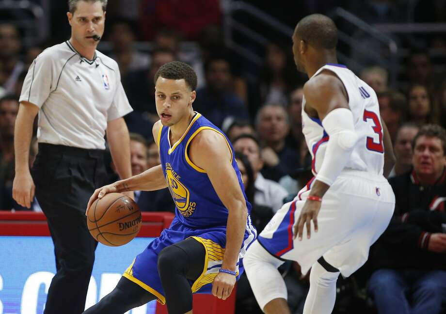 Golden State Warriors' Stephen Curry, left, prepares to dribble around his back causing Los Angeles Clippers Chris Paul, right, to fall to the court during the first half of an NBA basketball game, Tuesday, March 31, 2015, in Los Angeles. (AP Photo/Danny Moloshok) Photo: Danny Moloshok, Associated Press
