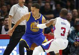 Golden State Warriors' Stephen Curry, left, dribbles behind his back while Los Angeles Clippers' Chris Paul, right, falls to the court during the first half of an NBA basketball game, Tuesday, March 31, 2015, in Los Angeles. (AP Photo/Danny Moloshok)