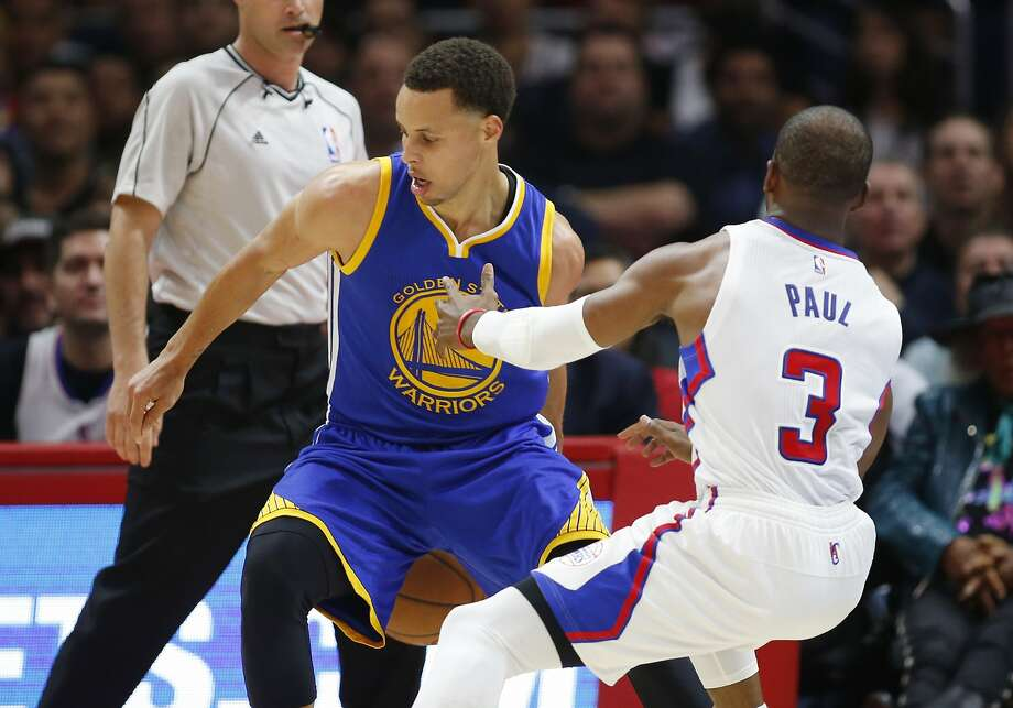 Golden State Warriors' Stephen Curry, left, dribbles behind his back while Los Angeles Clippers' Chris Paul, right, falls to the court during the first half of an NBA basketball game, Tuesday, March 31, 2015, in Los Angeles. Photo: Danny Moloshok, Associated Press