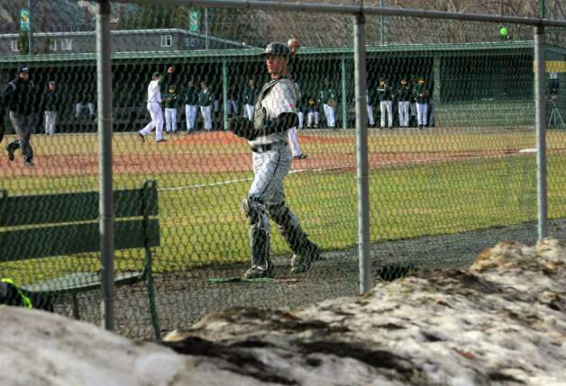 Army catcher Keegan Vega warm up just beyond a pile of icy snow during their college baseball game against Siena on Tuesday March 31, 2015 in Loudonville, N.Y. (Michael P. Farrell/Times Union) Photo: Michael P. Farrell / 00031246A