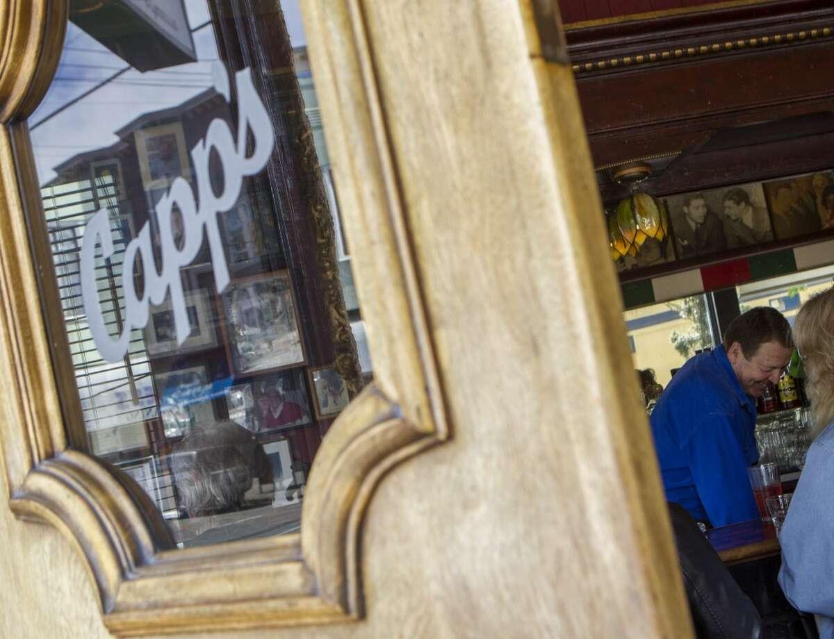 Bartender Randy Harris serves a customers at Capp's Corner, Friday, March 27, 2015, in San Francisco, Calif.