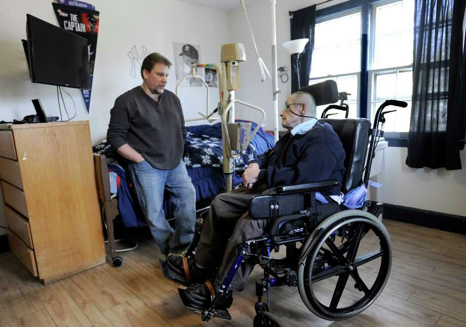 Victor Ocreene, left, a residential co-ordinator for Ability Beyond, visits with Tom Ackerson, 78, in his bedroom at a group home on Deer Hill Drive in danbury, Conn., Wednesday, April 1, 2015. Photo: Carol Kaliff / The News-Times