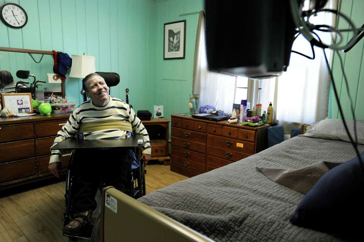 Peter Tanner, 53, watches TV in his room at an Ability Beyond home on Deer Hill Drive in Danbury, Conn., Wednesday, April 1, 2015.