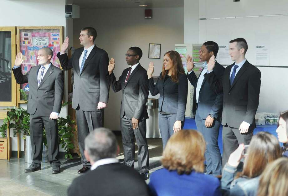 Police cadets, from left, Steve Orgera, Steve Estabrook, Kevin Lochard, Dili Santos, Kelli Reynolds and Conor Canning, raise their right hands as they are sworn in at the Government Center in Stamford, Conn. Wednesday, April 1, 2015. Photo: Tyler Sizemore / Greenwich Time