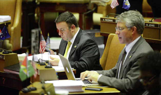 Assemblyman Karl Brabenec reads over bills from his seat in the Assembly Chamber before the start of session Monday afternoon, March 30, 2015, at the Capitol in Albany, N.Y. Assemblyman Phil Steck is seated right. (Will Waldron/Times Union) Photo: WW, Albany Times Union / 00031230A