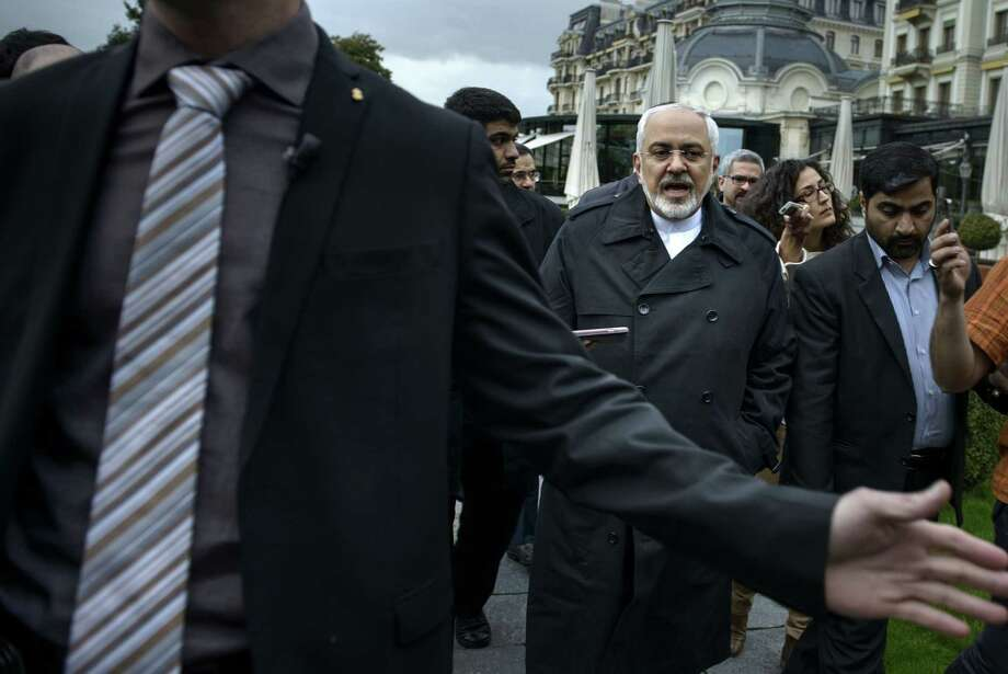 Iranian Foreign Minister Javad Zarif, centre right,  talks to members of the media while walking through a courtyard at the Beau Rivage Palace Hotel during an extended round of talks, Wednesday, April 1, 2015 in Lausanne, Switzerland. Negotiations over Iran's nuclear program appeared headed for double overtime on Wednesday, beset by competing claims after diplomats abandoned a March 31 deadline for the outline of a deal and agreed to press on. (AP Photo/Brendan Smialowski, Pool) Photo: Brendan Smialowski / Associated Press / POOL AFP