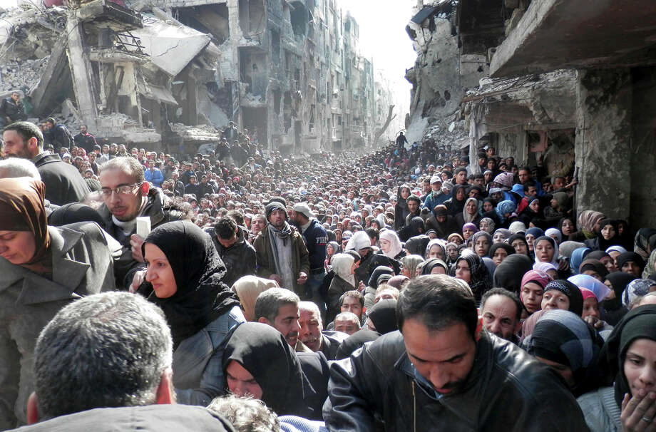 Residents of the besieged Palestinian camp of Yarmouk line up to receive food supplies outside Damascus. Islamic State militants have infiltrated the camp. Photo: Uncredited / Associated Press / UNRWA
