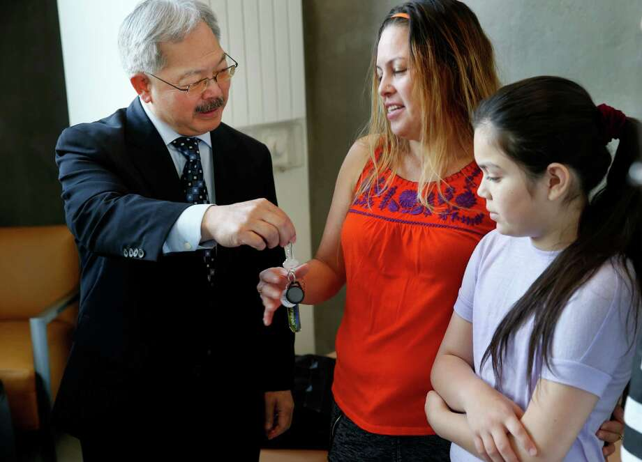 Mayor Ed Lee handed over the keys to Lidia Flores for her new apartment although she has been moved in for two weeks.  Her daughter Fatima Ulloa is at right. San Francisco Mayor Ed Lee welcomed the first occupants of the new Broadway Sansome family housing development in North Beach Wednesday April 1, 2015. Photo: Brant Ward / The Chronicle / ONLINE_YES