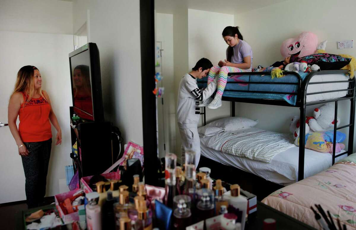 While mother Lidia Flores (left) answers questions about her new apartment, her son Christian Ulloa and daughter Fatima Ulloa share a quiet moment reflected in a mirror. San Francisco Mayor Ed Lee welcomed the first occupants of the new Broadway Sansome family housing development in North Beach Wednesday April 1, 2015.