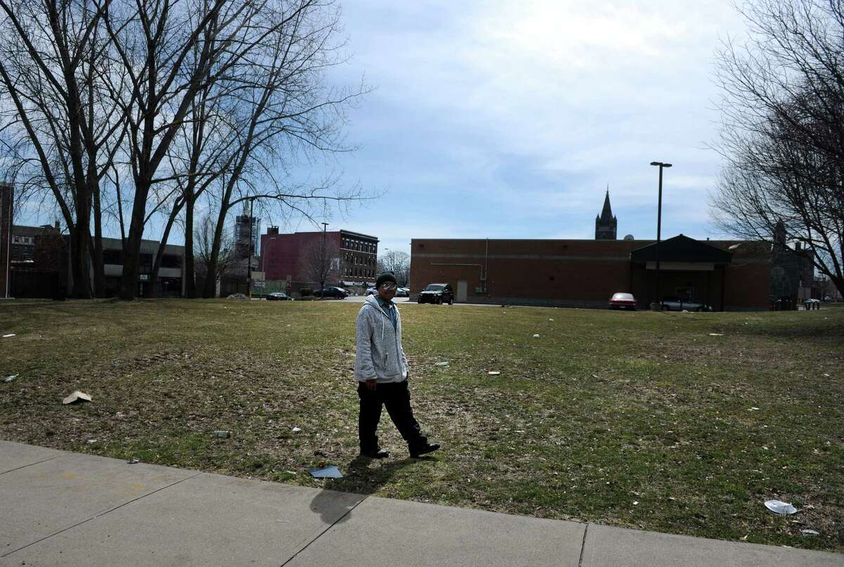 Natasha Pottinger walks past an open lot at 515 West Avenue in Bridgeport on her way home from work Wednesday, April 1, 2015. Bridgeport Neighborhood Trust is building a $12 million development that will include 48 housing units on the land which sits behind the Fairfield Avenue Walgreen's store.