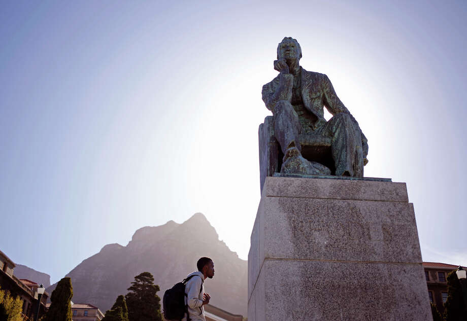 Students walk past a statue of British colonialist Cecil John Rhodes at the University of Cape Town. Protesters have tossed excrement on the statue. Photo: Schalk Van Zuydam / Associated Press / AP
