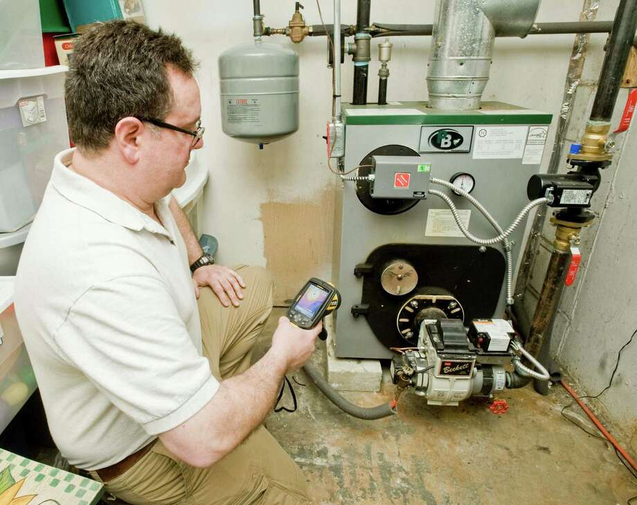 Tom Schlotter of Bethel, a home inspector, uses an infrared camera to check for heat and heat loss. Tuesday, March 31, 2015 Photo: Scott Mullin / The News-Times Freelance