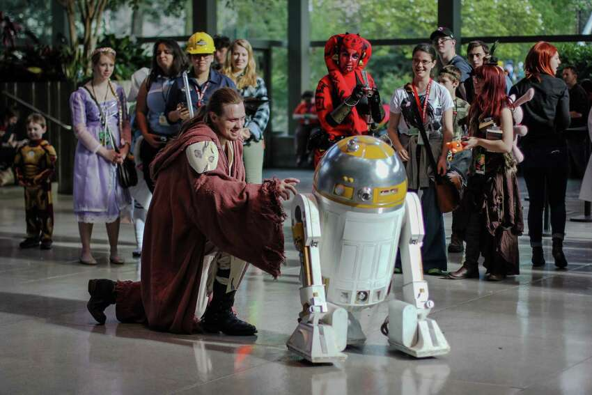 A Jedi interacts with a droid during day two of Emerald City Comicon at the Washington State Convention Center on Saturday, March 28, 2015. The three day convention is the largest comic book and pop culture convention in the Pacific Northwest. The convention features cosplay, comic books, celebrities and more.