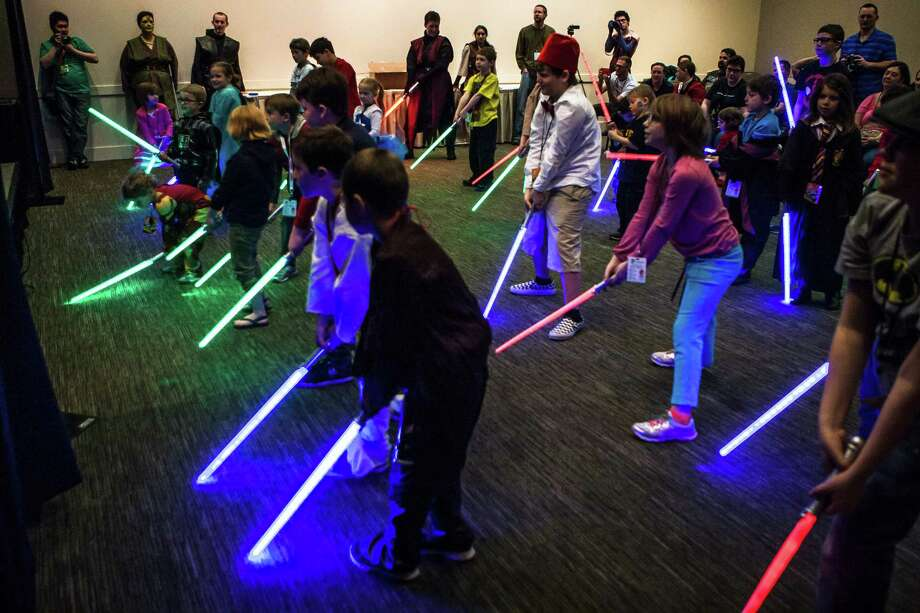 Children participate in a lightsaber demonstration during day two of Emerald City Comicon at the Washington State Convention Center on Saturday, March 28, 2015. The three day convention is the largest comic book and pop culture convention in the Pacific Northwest. The convention features cosplay, comic books, celebrities and more. Photo: DANIELLA BECCARIA, SEATTLEPI.COM / SEATTLEPI.COM