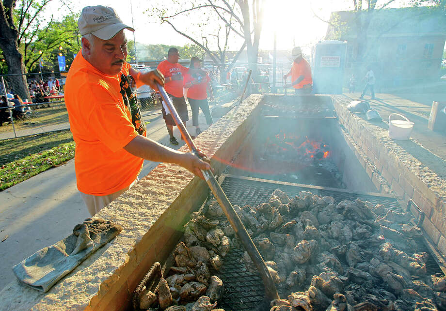 A worker turns the oysters on the pit during the 2014 Fiesta Oyster Bake at St. Mary's University. Photo: Tom Reel /San Antonio Express-News / San Antonio Express-News