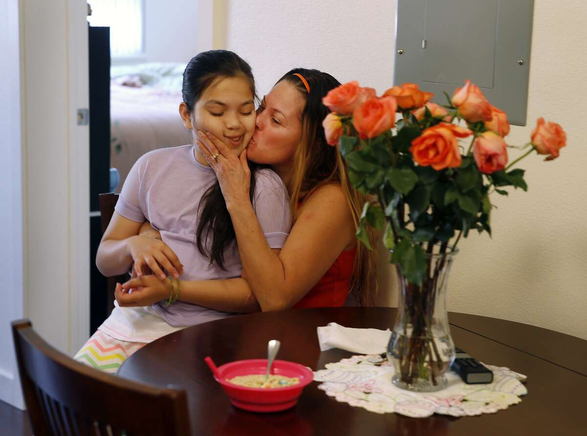Lidia Flores kisses her daughter Fatima Ulloa in the kitchen area of their new apartment after a ceremony. San Francisco Mayor Ed Lee welcomed the first occupants of the new Broadway Sansome family housing development in North Beach Wednesday April 1, 2015.