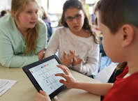 Marcos Zarta creates a table on an iPad with fellow fourth-graders Ashley D'Andrea, left, and Juliana Contadino during math class at North Mianus School in Greenwich, Conn. Wednesday, April 1, 2015.  Students and teachers use the Singapore math program, which uses concrete, pictoral and abstract steps and places emphasis on critical thinking and collaboration.