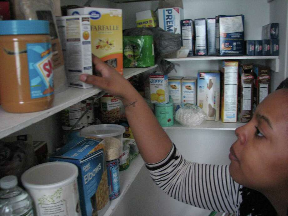 Jasmine Robinson looks for Kosher for Passover items in the pantry she shares with her roommates. She will be keeping those items in a separate container for Passover. (James King/Times Union)