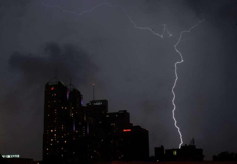 Lightning strikes over downtown San Antonio after the Fiesta Flambeau Night Parade on Saturday, April 27, 2013. Photo: Billy Calzada, Staff / San Antonio Express-News / © 2013 San Antonio Express-News