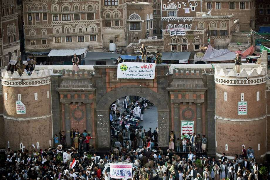 Shiite rebels known as Houthis stand guard on the gate of Bab al-Yemen, the entrance of the old city of Sanaa, as their comrades protest against Saudi-led airstrikes, during a rally in Sanaa, Yemen, Wednesday, April 1, 2015. Saudi-led coalition warplanes bombed Shiite rebel positions in both north and south Yemen early Wednesday, setting off explosions and drawing return fire from anti-aircraft guns. (AP Photo/Hani Mohammed) Photo: Hani Mohammed, STR / AP