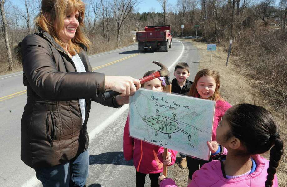 Altamont Elementary School art teacher Trisha Zigrosser, left, and second grade students. left to right, Gracie Wilcox, Keegan Feeley, Addison Dover and Choloe Tyson put up save our salamander signs along Picard Road on Wednesday April 1, 2015 in Altamont, N.Y. (Michael P. Farrell/Times Union) Photo: Michael P. Farrell / 00031244A