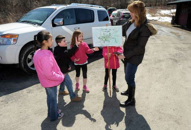 Altamont Elementary School art teacher Trisha Zigrosser, right, and second grade students put up save our salamander signs along Picard Road on Wednesday April 1, 2015 in Altamont, N.Y. (Michael P. Farrell/Times Union) Photo: Michael P. Farrell / 00031244A