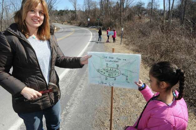 Altamont Elementary School art teacher Trisha Zigrosser, left, and second grade student Choloe Tyson put up save our salamander signs along Picard Road on Wednesday April 1, 2015 in Altamont, N.Y. (Michael P. Farrell/Times Union) Photo: Michael P. Farrell / 00031244A