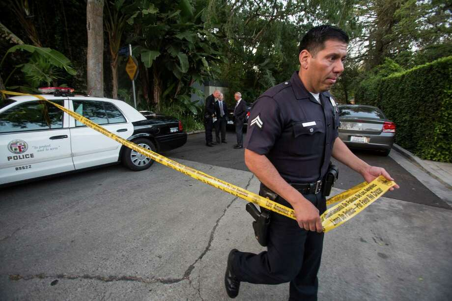 A police officer creates a perimeter outside a home in the Hollywood Hills area of Los Angeles, Tuesday, March 31, 2015. Police say a man was found dead at the home of Andrew Getty, heir to Getty oil fortune. (AP Photo/Ringo H.W. Chiu) Photo: Ringo H.W. Chiu, FRE / FR170512 AP