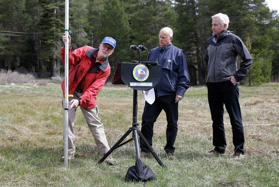 Frank Gehrke, left, chief of the California Cooperative Snow Surveys Program for the Department of Water Resources, points to a mark on the snow pack measuring pole that was the lowest previous snow pack level as  Gov. Jerry Brown, center and Mark Cowin, director of the Department of Water Resources look on at a news conference near Echo Summit, Calif., Wednesday, April 1, 2015. Gehrke said this was the first time since he has been conducting the survey at that he found no snow at this location at this time of the year.  Brown took the occasion to announce that he signed an executive order requiring the state water board to implement measures in cities and towns to cut water usage by 25 percent compared with 2013 levels. (AP Photo/Rich Pedroncelli) ORG XMIT: CARP106 Photo: Rich Pedroncelli / AP
