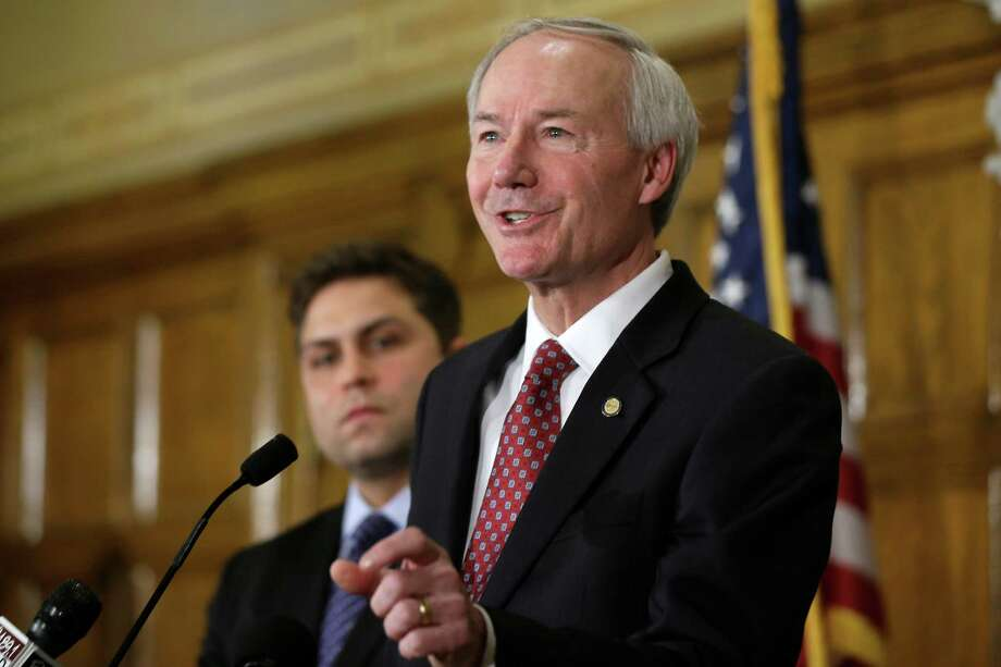 Arkansas Gov. Asa Hutchinson answers reporters' questions as Sen. Jonathan Dismang, R-Beebe, background, listens at the state Capitol in Little Rock, Ark., Wednesday, April 1, 2015. Hutchinson called for changes to the state's religious objection measure facing a backlash from businesses and gay rights groups, saying it wasn't intended to sanction discrimination based on sexual orientation. (AP Photo/Danny Johnston) ORG XMIT: ARDJ101 Photo: Danny Johnston / AP