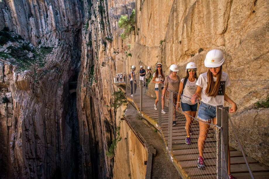 Tourists walk along the 'El Caminito del Rey' (King's Little Path) footpath on April 1, 2015 in Malaga, Spain. 'El Caminito del Rey', which was built in 1905 and winds through the Gaitanes Gorge, reopened last weekend after a safer footpath was installed above the original. The path, known as the most dangerous footpath in the world, was closed after two fatal accidents in 1999 and 2000. The restoration started in 2011 and reportedly cost 5.5 million euros. Photo: David Ramos, Getty Images / 2015 Getty Images
