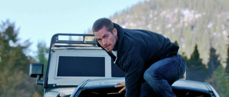 """This photo provided by Universal Pictures shows Paul Walker as Brian in a scene from """"Furious 7.""""  When the high-speed action sequel """"Furious 7"""" debuts this weekend, audiences at Hollywood's famous TCL Chinese Theatre will see every tire skid and fist fight in Imax's brand-new laser format. (AP Photo/Universal Pictures) Photo: Universal Pictures, HONS / Associated Press / Universal Pictures"""