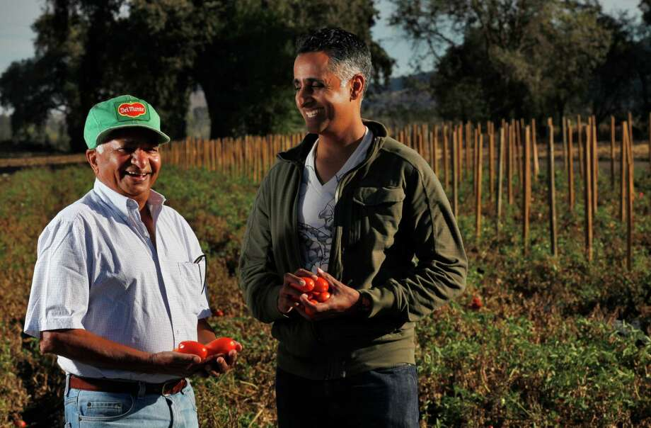 Director Sanjay Rawal, 39, right, poses for a portrait with his father Dr. Kanti Rawal, 74, left, Oct. 22, 2014 at the VoloAgri Group Inc. tomato breeding station research fields in Morgan Hill, Calif. Sanjay Rawal directed a documentary called Food Chains that is about the massive food industry and the toll it can take on the workers in the fields. It focuses on a group of tomato pickers in Florida and follows their journey as they fight for their rights. Sanjay grew up in San Leandro and spent his summers in the fields with his father who is a tomato breeder. Photo: Leah Millis, Staff / The Chronicle / ONLINE_YES