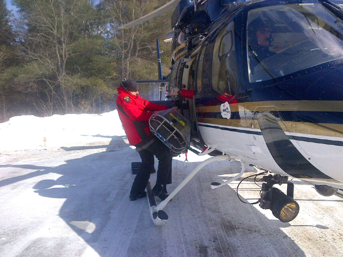 Forest Rangers offload a seven-year-old boy from a State Police helicopter. The boy, his eleven year old brother, and mother spent the night lost on Mount Marcy over the weekend and had to be rescued. On Sunday, Jan. 14, 2018, rangers used a helicopter to rescue an injured snowboarder from Mount Marcy. (New York State DEC) ORG XMIT: dADL-1k5s3mTzB_qzika
