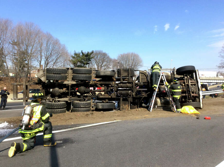 Firefighters work to extricate the driver of a tractor-trailer after his truck collided with the Kings Hwy overpass, coming to rest on its drivers side. The driver was killed in the accident that occurred on I-95 North near the Exit 23 off ramp in Fairfield, Conn. on Thursday, April 2, 2015. Photo: Contributed Photo, Fairfield Fire Dept. / Connecticut Post Contributed