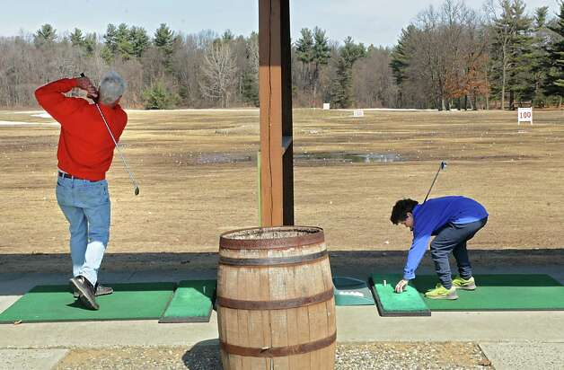 Dean Bouton of Guilderland and Rowan Healy, 10, who is up from Maryland visiting his grandparents, practice their golf swings at the Northway Golf Center driving range Thursday, April 2, 2015 in Clifton Park, N.Y.  (Lori Van Buren / Times Union) Photo: Lori Van Buren