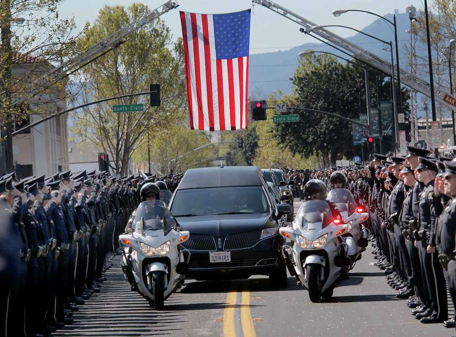 The hearse carrying Michael Johnson made its way past hundreds of saluting San Jose police officers Thursday April 2, 2015. The memorial service for slain San Jose police officer Michael Johnson drew thousands of law enforcement officers, fire fighters and friends from across the state to the SAP Center. Photo: Brant Ward / The Chronicle / ONLINE_YES